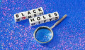 Black holes text in uppercase letters inscribed on small white cubes with hand magnifier nearby blue dotted background Royalty Free Stock Photos