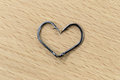 The black hooks placed heart symbols on wood background Royalty Free Stock Photography