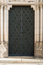 Black iron cathedral door ornate set in white stone Royalty Free Stock Image