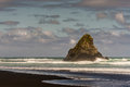 Black Karekare Beach with the Watchman Rock. Royalty Free Stock Photo
