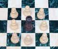 The black king surrounded by white pawns chess pieces on chessboard Stock Photos