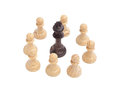 Black king surrounded by white pawns wooden chess piece on chessboard Royalty Free Stock Photo