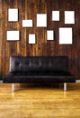 Black leather couch against wooden covered wall many empty picture frames Stock Photos
