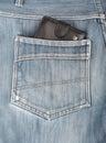 Black leather wallet sticking in the back pocket of denim jeans blue Stock Image