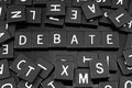 Black letter tiles spelling the word & x22;debate& x22; Royalty Free Stock Photo