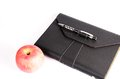 Black luxury organizer and black pen with apple isolated on white background Stock Images