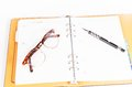 Black luxury organizer and black pen with glasses isolated on white background Royalty Free Stock Photo
