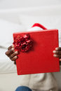 Black man covering his face with gift Royalty Free Stock Photo