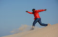 Black man running down dune full body of an african american young with happy smiling facial expression jumping and a barefooted Stock Photography