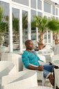 Black man sitting at a bar handsome fit alone street terrace summer outdoors Royalty Free Stock Image
