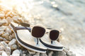 Black mirrored sunglasses on a stones. Shadow from glasses. Sunlight. Summer concept. Royalty Free Stock Photo