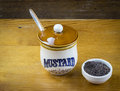 Black mustard seeds and mustard pot on wood table Royalty Free Stock Photo