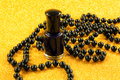 Black nail varnish a closeup of and beads on a sparkly gold background Royalty Free Stock Image