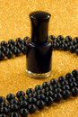 Black nail varnish a closeup of and beads on a sparkly gold background Stock Photo