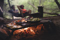 Black Non Stick Pan on Black Metal Charcoal Griller With Steak on Outdoor Forest With Two Persons Seating on Hammock Stockfotografie