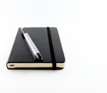 Black notebook with pen isolated white background Stock Photography