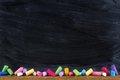 Black old empty chalkboard for copy space with colorful pieces of chalk Stock Photo