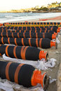 Black orange oil gas pipes lying beach ready transport Stock Photos