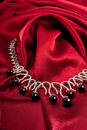Black pearls on red textile Royalty Free Stock Photo