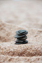 Black pebble tower of pebbles stacked on beach sand Royalty Free Stock Photo