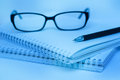 Black pen and glasses lying on notebook close up blue color Stock Image