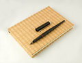 Black pen and notebook on white background Royalty Free Stock Image