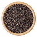 Black pepper corns in wooden bowl isolated on white background Royalty Free Stock Photo
