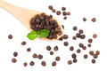 Black peppercorn in a wooden spoon isolated on white background. Top view