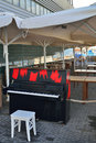 Black piano with red spots israel morning in the port of jaffa many large umbrellas under a canopy and tables and and white Stock Photo