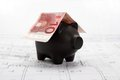 Black piggy bank with roof of ten euro note on house drawing Stock Photo