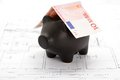 Black piggy bank with roof of ten euro note on house drawing top view Royalty Free Stock Photos