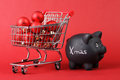Black piggy bank with white text xmas and full shopping basket of red matt and glossy christmas balls on red background horizontal Stock Image