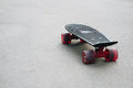 Black plastic skateboard with red wheels on asphalt