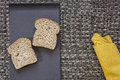Black plate with bread and yellow napkin on warp background Royalty Free Stock Photo