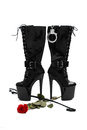 Black platform boots with whip and rose isolated on white Royalty Free Stock Photo