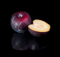 Black plum on background with reflection Royalty Free Stock Photos