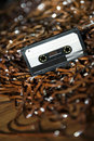 Black recordable plastic audio cassette resting large amount magnetic audio tape selective focus foreground Royalty Free Stock Photo