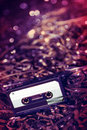 Black recordable plastic audio cassette resting on a large amount of magnetic audio tape selective focus on foreground Royalty Free Stock Image