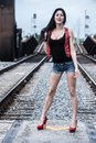 Black and red railroad theme shoot attractive young dark haired model with track background Stock Image
