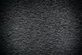 Black revetment wall putty high contrasted with vignetting effect macro texture background Stock Photos