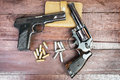 Black revolver gun and semi automatic mm gun on wooden background Royalty Free Stock Images