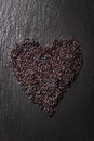 Black rice in heart shape on a black stone background with water droplets Royalty Free Stock Photo