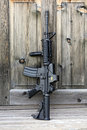The black rifle ar assault carbine m a with holographic sight against an old wooden door vertical composition Stock Image