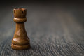Black rook chess piece on a wooden table brown and background Royalty Free Stock Photos