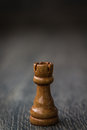 Black rook chess piece on a wooden table brown and background Royalty Free Stock Photo