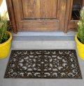 Black Rubber Scraper Floor Mat Indoor Outdoor door mat outside home with yellow flowers and leaves Royalty Free Stock Photo