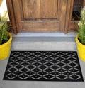 Black Rubber Scraper Floor Mat Indoor Outdoor door mat with yellow flowers and leaves Royalty Free Stock Photo
