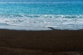 Black sand volcanic beach with white foam sea wave Royalty Free Stock Photo