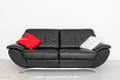 Black settee a sofa with red and white cushion Royalty Free Stock Image