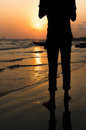 A black silhouette of a man standing at the sunrise beach Stock Images